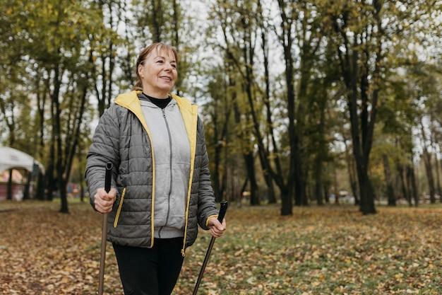 Смайлик старшая женщина с треккинговыми палками на открытом воздухе и копией пространства