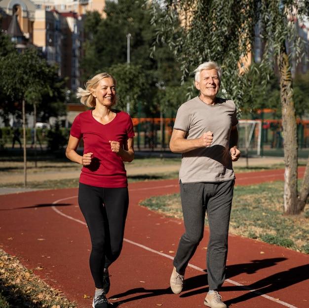 Smiley elderly couple jogging outdoors