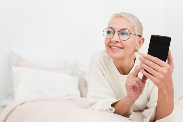 Smiley elderly woman in bed holding smartphone