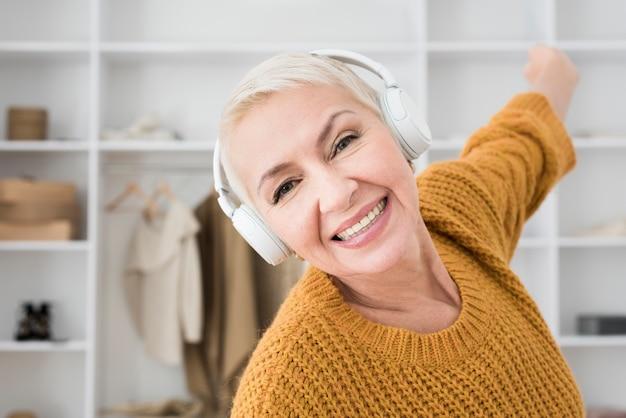 Улыбающаяся пожилая женщина наслаждается музыкой в наушниках