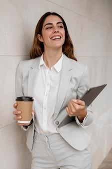 タブレットとコーヒーカップを保持しているスマイリーエレガントな実業家