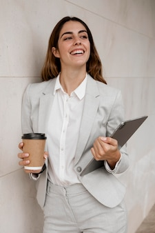 Smiley elegant businesswoman holding tablet and coffee cup