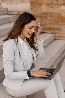 Donna di affari elegante di smiley con smartwatch che lavora al computer portatile all'aperto