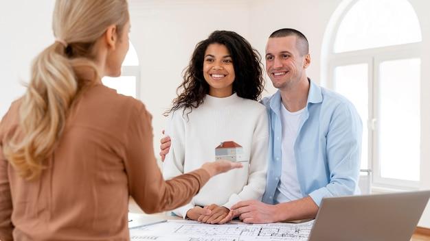 여성 부동산 중개인과 대화하는 웃는 포옹 커플