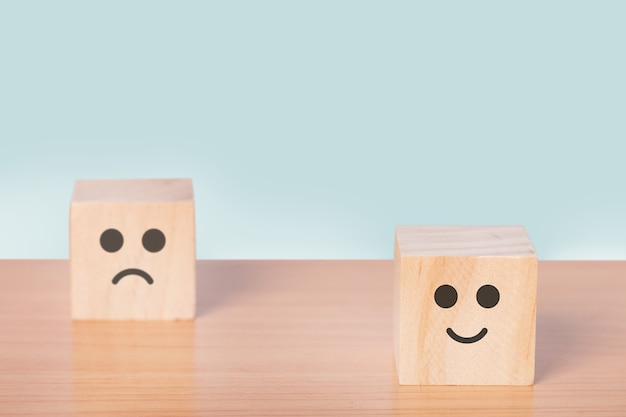 Smiley face and blurred sad face icon on the wood cube, customer service rating, satisfaction survey concept.