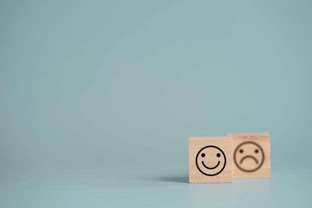 Smiley face in front of sadness face which print screen on wooden cube block, emotion selection for customer satisfaction and evaluation concept.