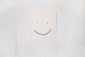 Смайлик на белой бумажной палочке на стене с лентой