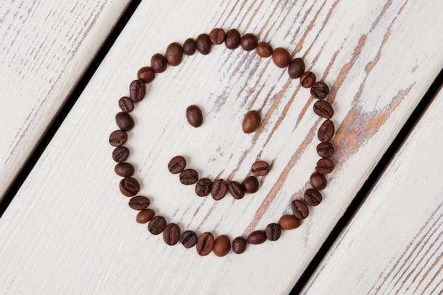 흰색 나무에 커피 콩으로 만든 웃는 얼굴. 원 모양과 미소 감정을 형성하는 상위 뷰 갈색 씨앗.