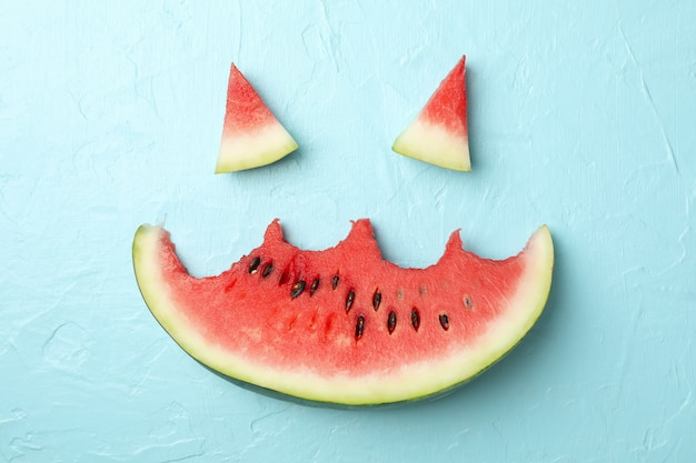 Smiley face made of watermelon on blue, top view