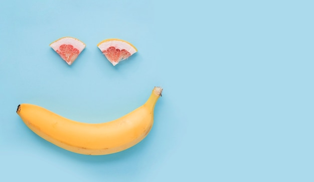 Smiley face made with yellow banana and slice of grapefruit on blue background