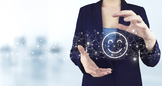Рейтинг смайлика для опроса удовлетворенности. две руки, держащей виртуальный голографический смайлик значок с легким размытым фоном. исследование удовлетворенности бизнесом.