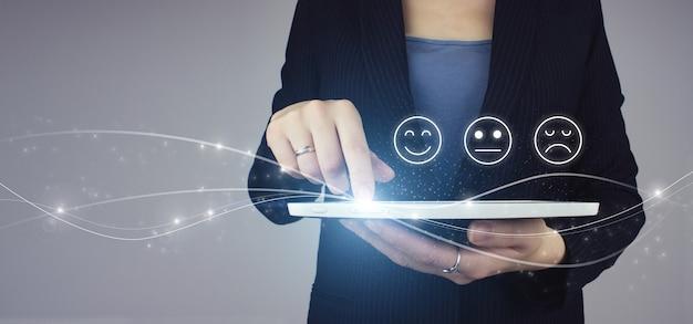 Рейтинг смайликов для опроса удовлетворенности. белая таблетка в руке коммерсантки с цифровым знаком эмоции стороны голограммы на сером фоне. концепция клиентского опыта.