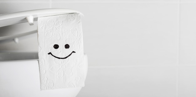 Smiley face on toilet paper roll