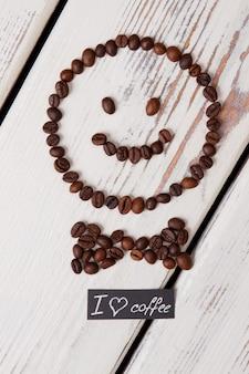 커피 콩으로 만든 나비 넥타이와 웃는 얼굴. 표면에 흰색 나무입니다.