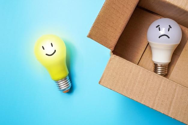 웃는 얼굴 노란색 전구는 상자 밖에 있고 흰색은 슬프게도 얼굴 전구는 상자 안에 있습니다.