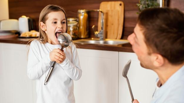 道具と一緒にキッチンで楽しんでいるスマイリーの父と娘