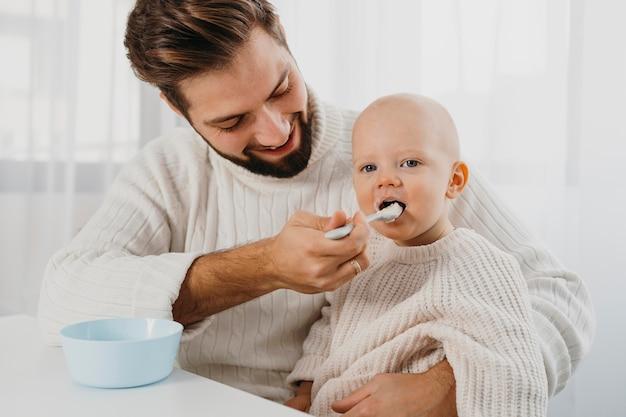 赤ちゃんに餌をやるスマイリーの父
