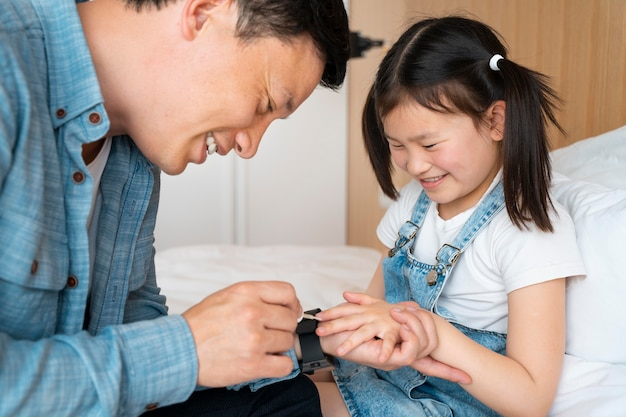 Smiley father painting girl's nails
