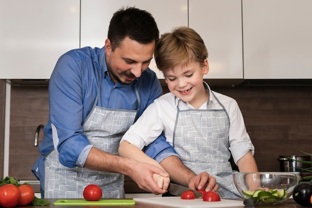 Smiley father and son cutting vegetables