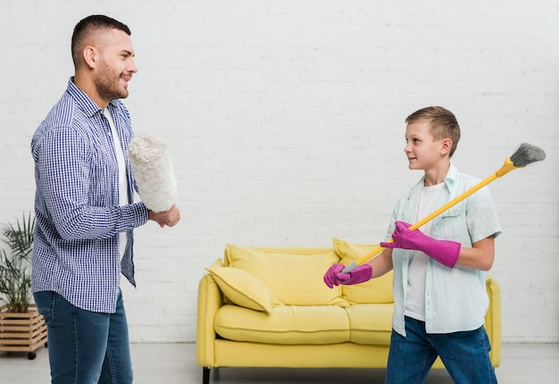 Smiley father and son play fight with duster and broom