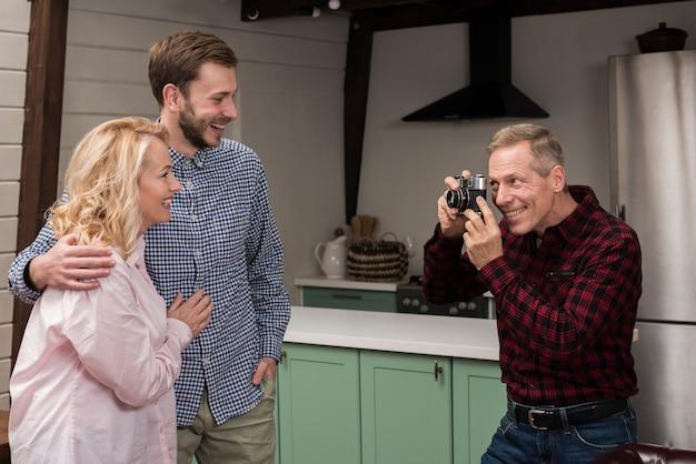 Улыбающийся отец фотографирует маму и сына на кухне
