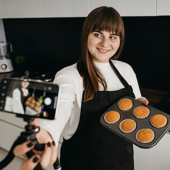 Smiley female blogger recording herself with smartphone while preparing muffins
