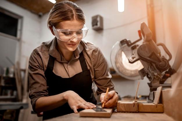 Falegname femminile di smiley che lavora nello studio