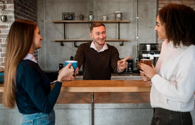 Colleghi femminili di smiley che mangiano caffè durante una riunione