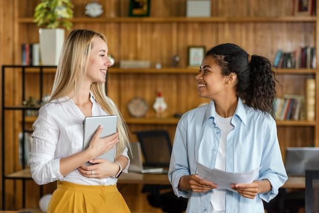 Улыбающиеся женщины-коллеги разговаривают на работе