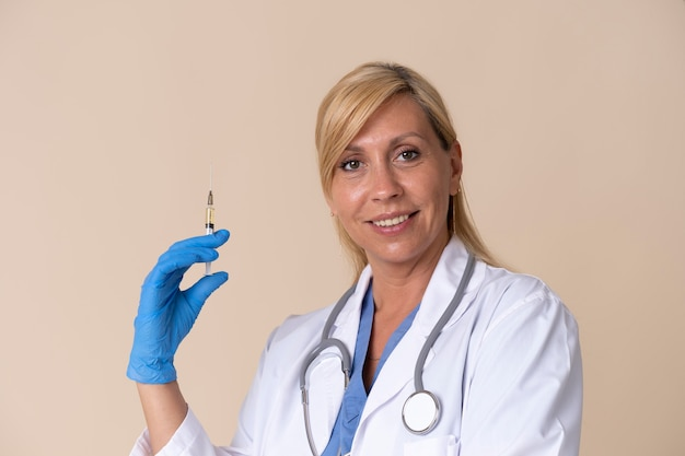 Medico femminile sorridente che tiene una siringa del vaccino vaccine