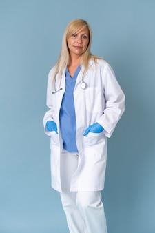 Medico femminile sorridente che posa in vestito e stetoscopio