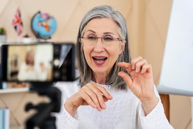 Insegnante di inglese femminile sorridente che fa lezioni online sul suo smartphone