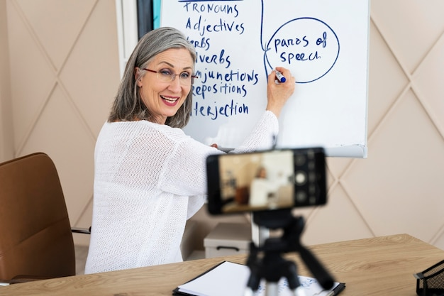 Учитель английского языка смайлик делает онлайн-уроки на своем смартфоне
