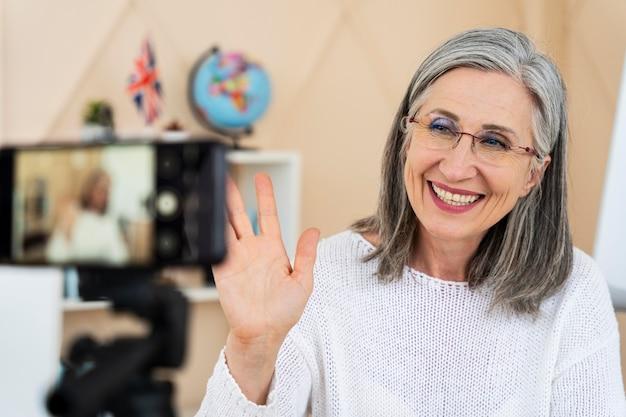 그녀의 스마트 폰에서 온라인 수업을 하 고 웃는 여성 영어 교사