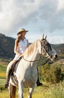 Smiley female farmer horseback riding in nature
