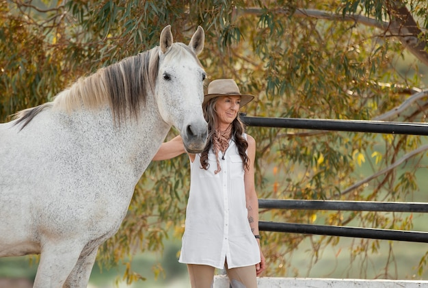 Coltivatore femminile di smiley che accarezza il suo cavallo
