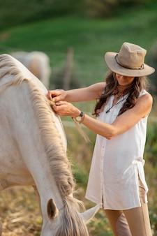 Смайлик женщина-фермер, лаская ее лошадь