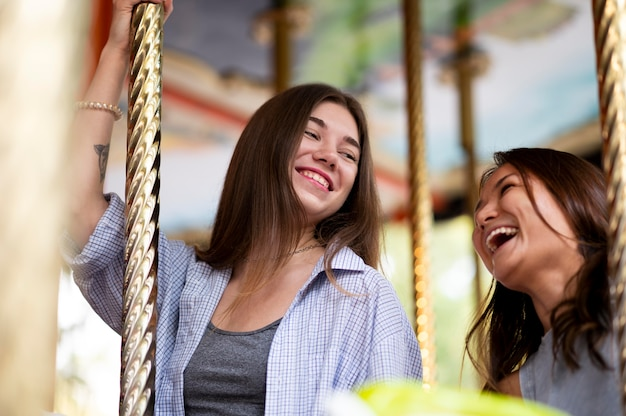 Smiley female friends on the carousel