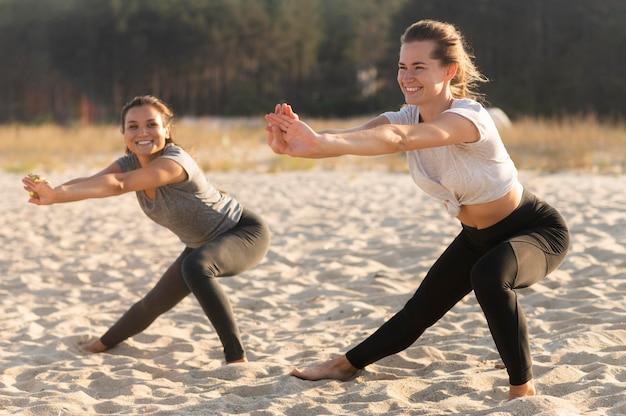 ビーチで運動するスマイリー女友達