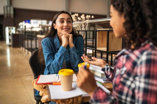 Улыбающиеся подруги пьют кофе и вместе делают домашнее задание
