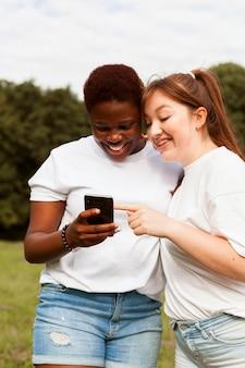 スマートフォンを屋外で見ている笑顔の女性の友人