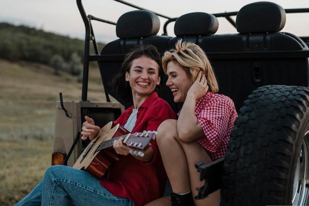 Amici femminili di smiley suonare la chitarra mentre si viaggia in auto