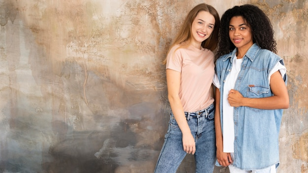 Smiley female friends posing together with copy space
