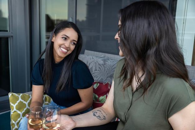 一緒に時間を過ごし、テラスでワインを飲むスマイリーの女性の友人