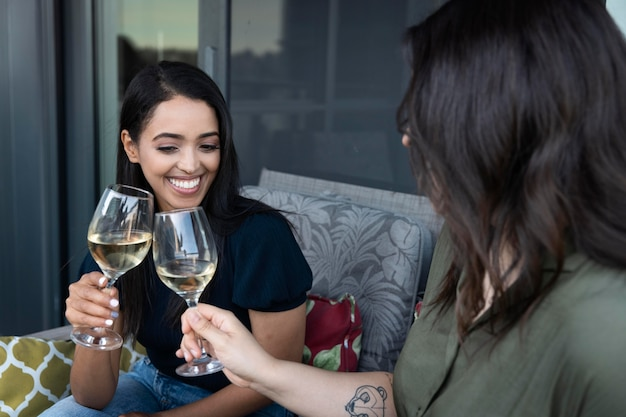 Smiley female friends spending time together and drinking wine at a terrace