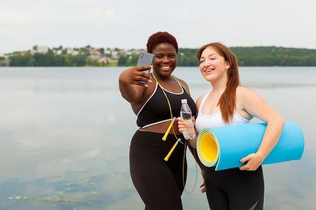 Улыбающиеся подруги, делающие селфи на открытом воздухе во время тренировки