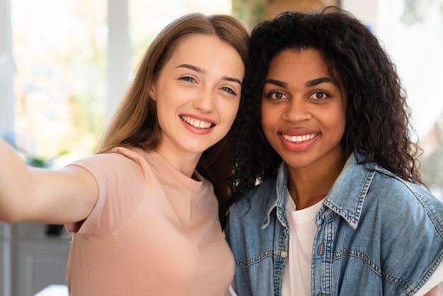 Amici femminili di smiley che prendono insieme un selfie
