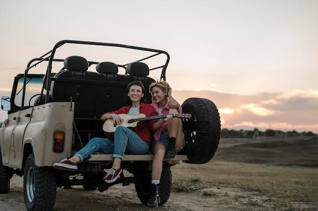 Amici femminili di smiley che viaggiano in macchina e suonare la chitarra