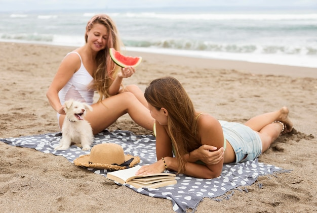 Smiley female friends with dog eating watermelon at the beach