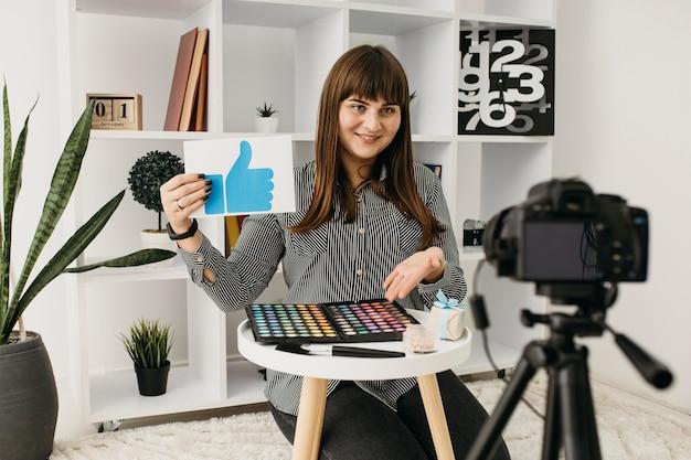 Blogger femminile di trucco di smiley con lo streaming a casa con la macchina fotografica